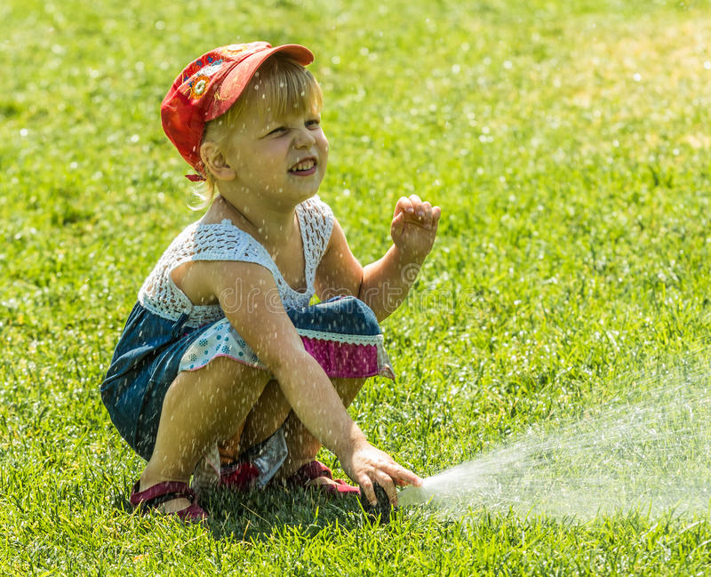Little girl holding during irrigation, spray stock photos
