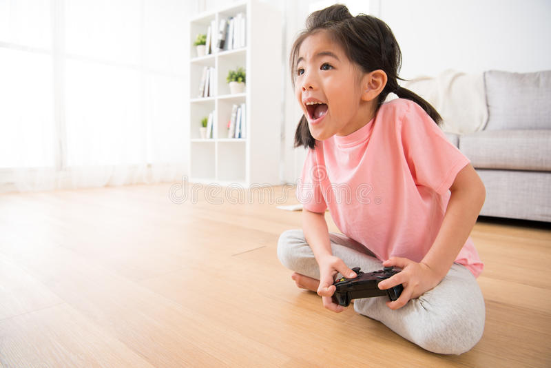 Little girl holding joystick happy play video game stock photography