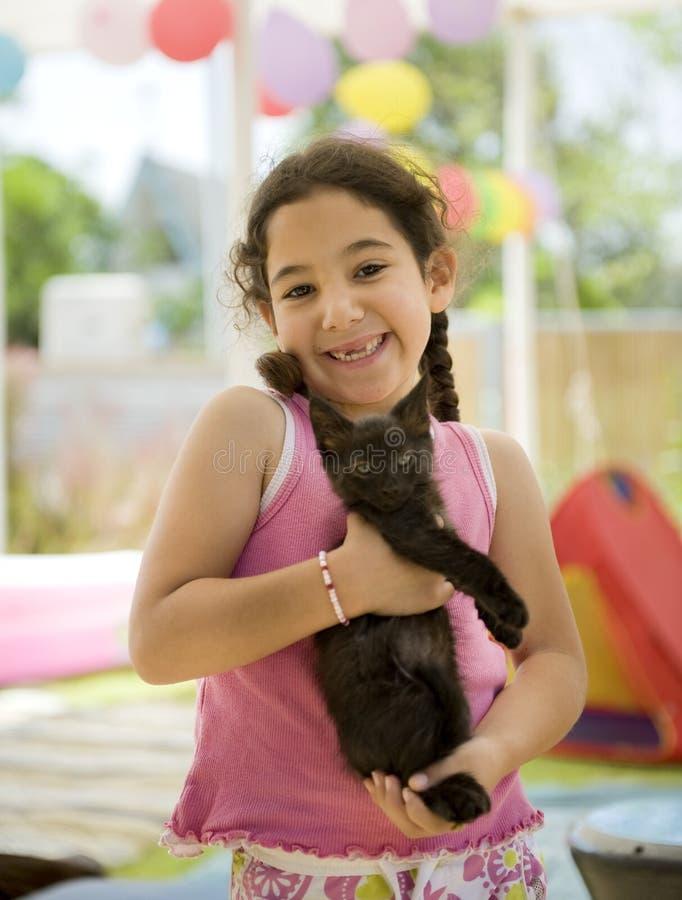 Little girl holding a kitten royalty free stock image