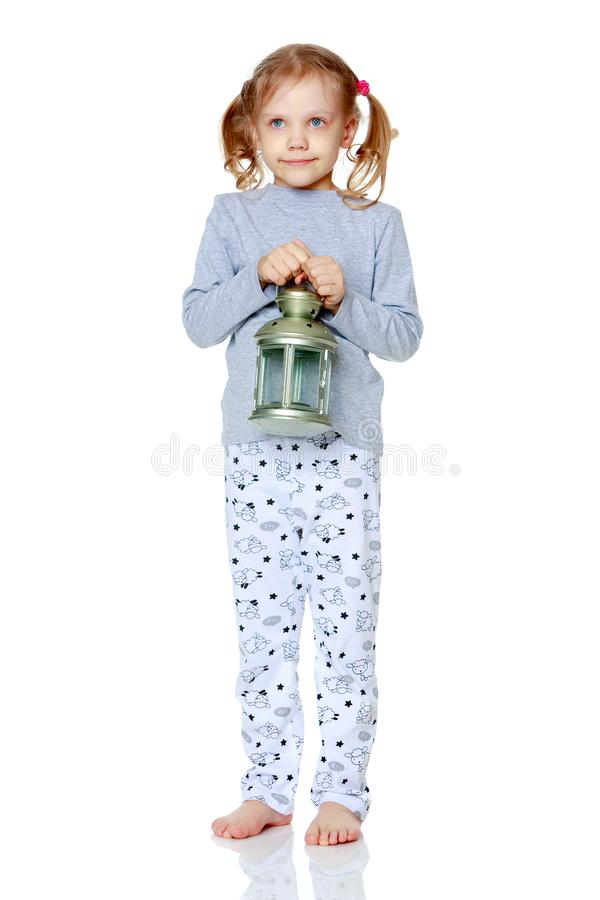A little girl is holding a lamp. stock photography