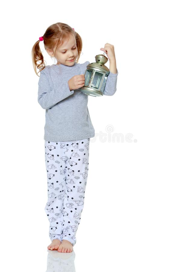 A little girl is holding a lamp. stock images