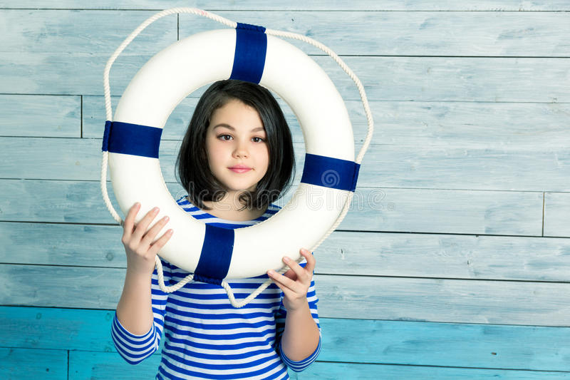 Little girl holding a lifebuoy and laughing royalty free stock photography