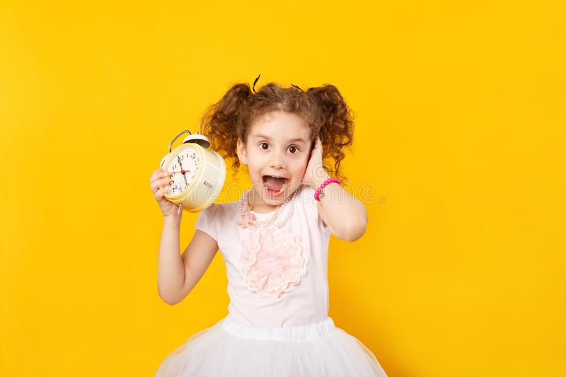 Little girl holding in one hands a big clock, another covering ear not to hear alarm, over yellow background. royalty free stock image