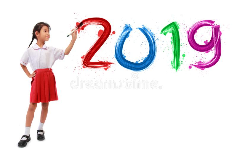 Little girl holding a paint brush painting happy new year 2019. On a white wall background, Back to school idea concept royalty free stock photo