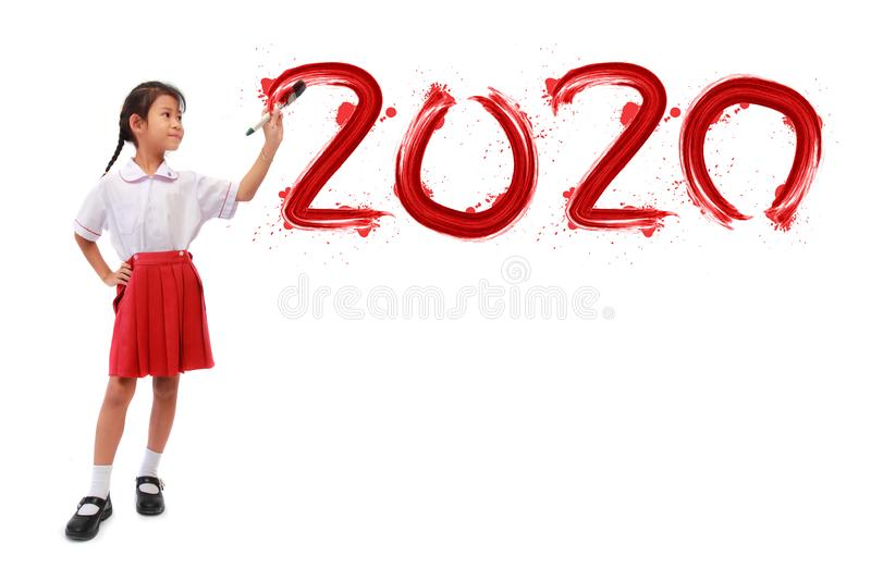 Little girl holding a paint brush painting happy new year 2020 on a white board royalty free stock photography