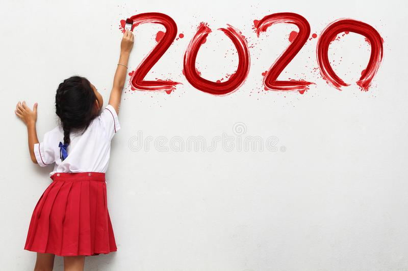 Little girl holding a paint brush painting happy new year 2020 on a white board royalty free stock photos