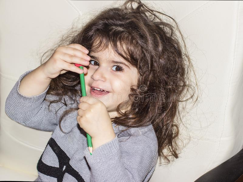 A little girl  is holding a pencil and smiling . close-up portrait of a three-year-old girl. stock photo