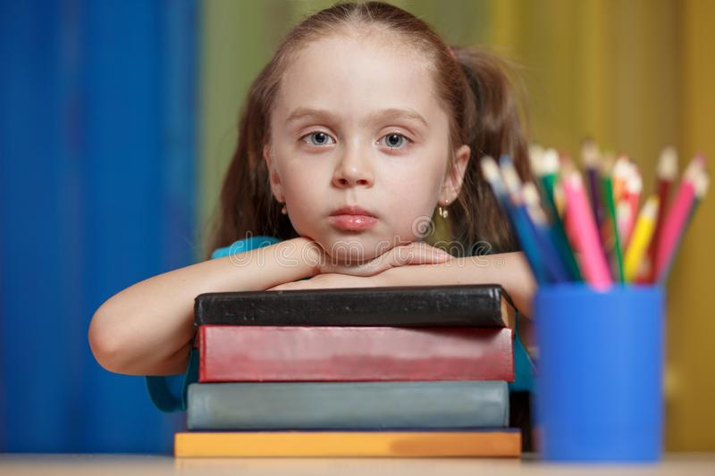 Little girl with books in school stock photography