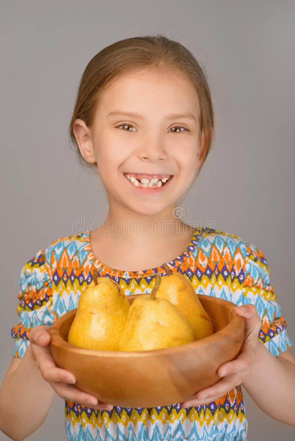 Little girl holding plate of yellow pears stock images