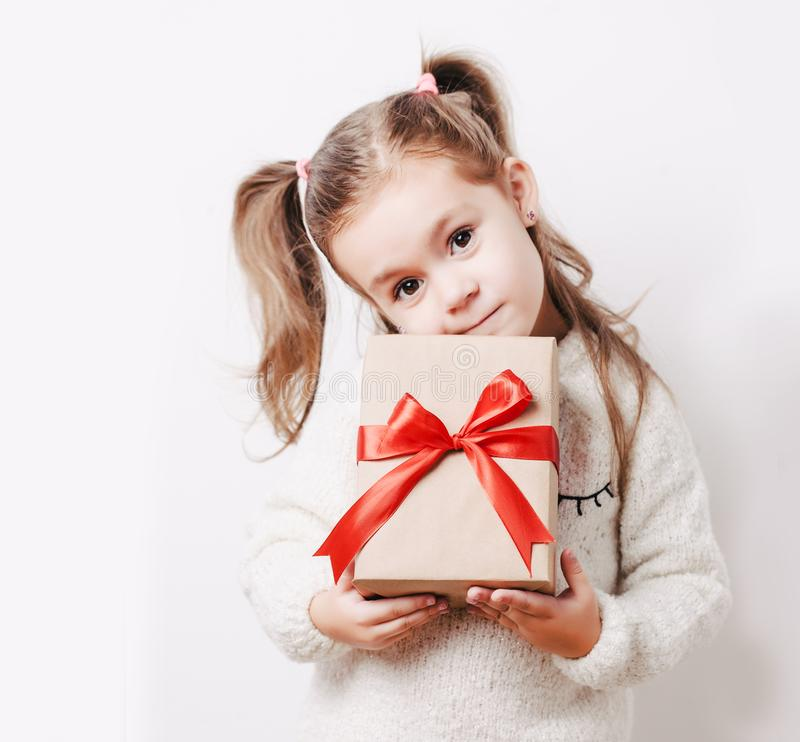 Little girl holding present box wrapped in kraft paper with big red bow. Christmas, new year or birthsday concept royalty free stock photography