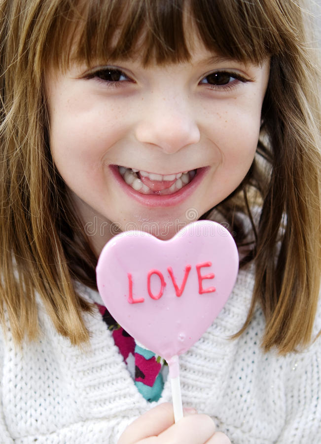 Little girl holding a red heart stock image