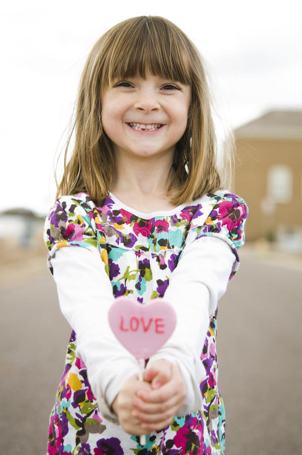 Little girl holding a red heart stock photo