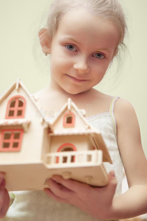Little girl holding scale house model. Portrait of young little girl holding scale house model showing dreaming facial expression. isolated stock photo