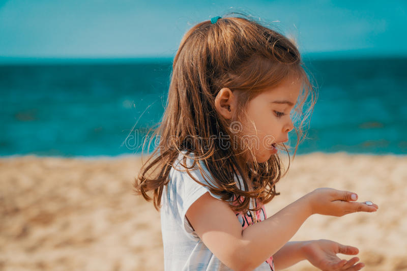 Little girl is holding a sea shell on the beach royalty free stock photo