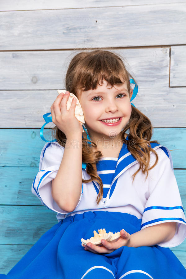 Little girl holding a seashell and laughs royalty free stock photo