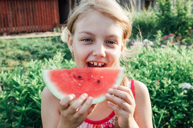 Little girl holding a slice of ripe red watermelon stock photo