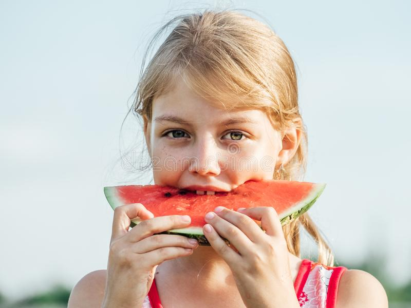 Little girl holding a slice of ripe red watermelon stock photography