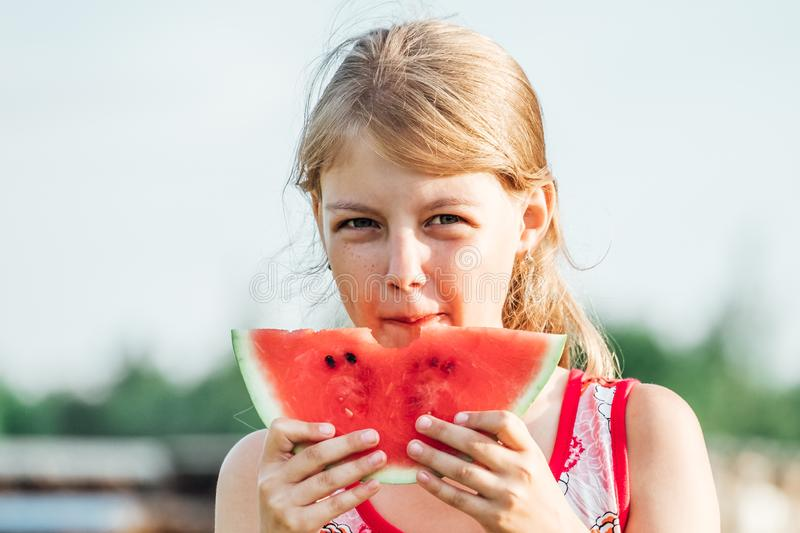 Little girl holding a slice of ripe red watermelon royalty free stock photography