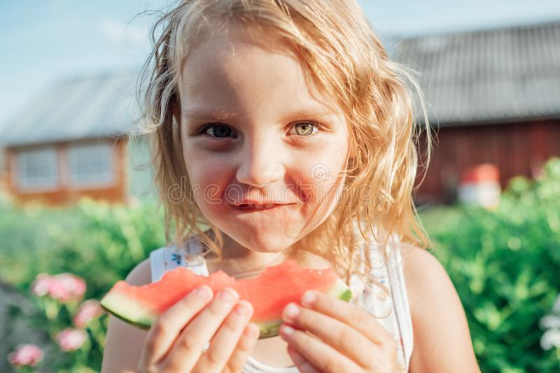 Little girl holding a slice of ripe red watermelon royalty free stock image