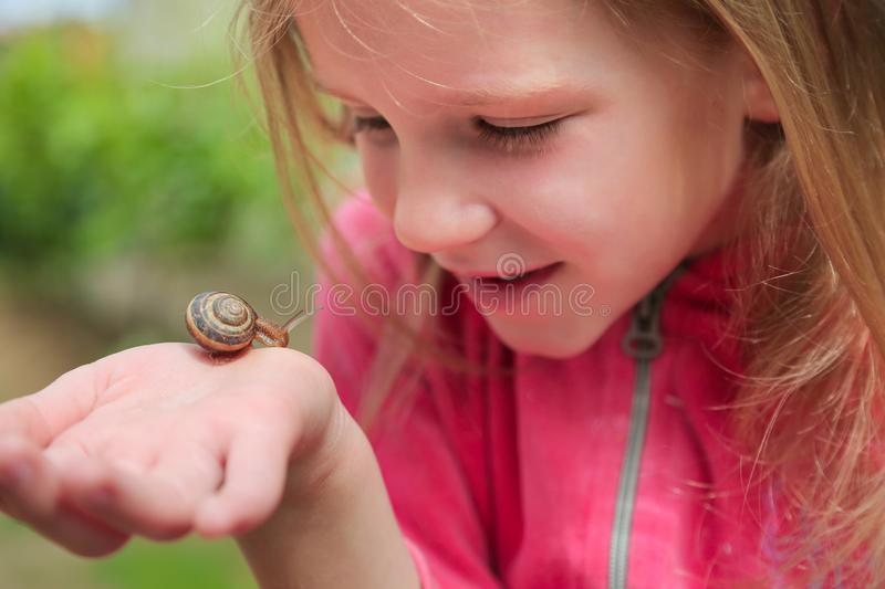 Little girl holding snails on her hand royalty free stock photography