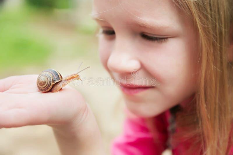 Little girl holding snails on her hand. Beautiful blond little girl watching and holding snails on her hand stock image