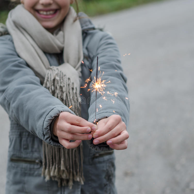 Little girl holding a sparkler. Outdoors Concept royalty free stock image