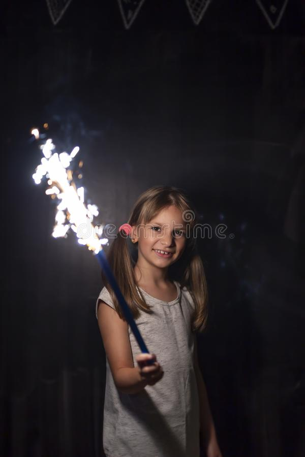 Little girl holding a sparkler. Portrait of a beautiful little girl having fun while holding a sparkler on Christmas Eve royalty free stock images