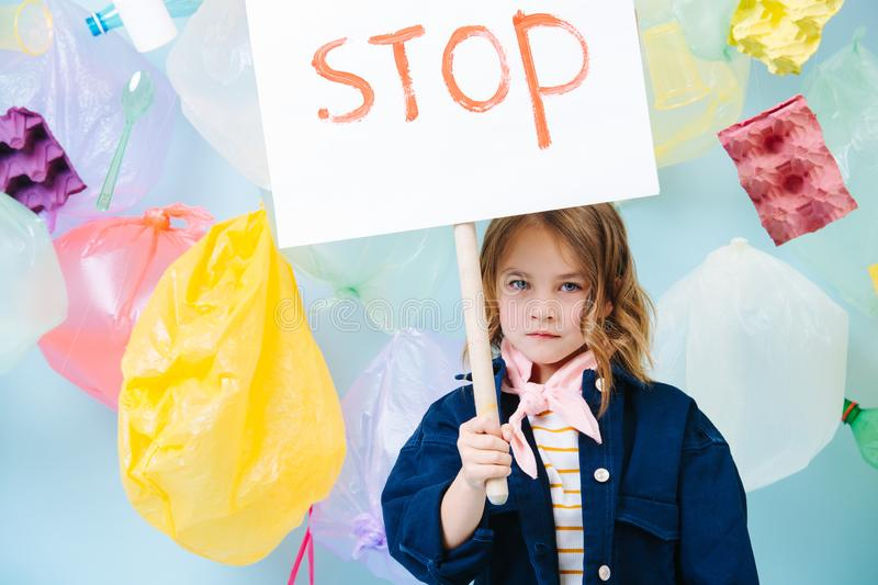 Little girl holding stop sign in protest against pollution and waste crisis royalty free stock photo