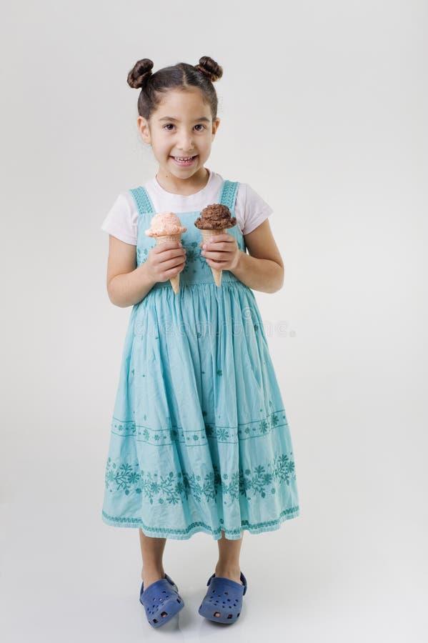 Little girl holding two ice cream cones