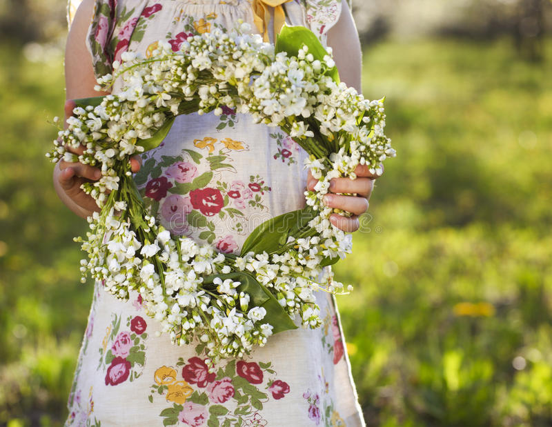 Little girl holding wreath from lily of the valley stock images