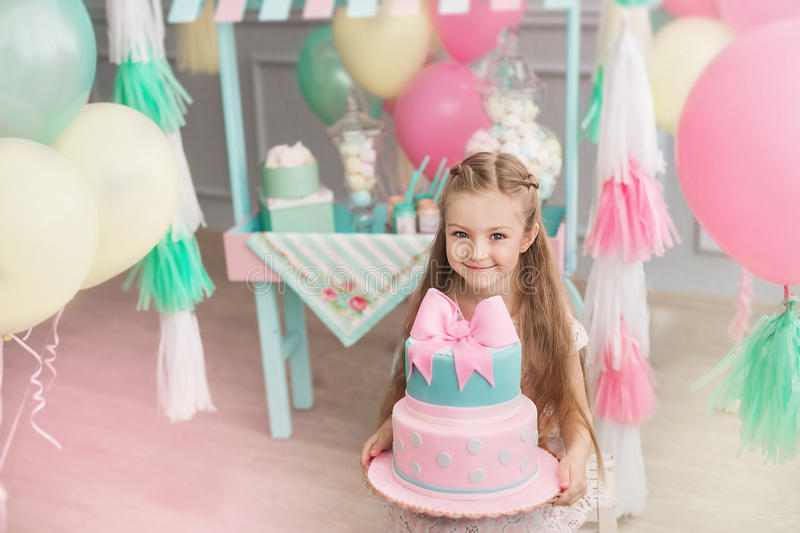 Little girl holds a big cake in a decorated room stock images