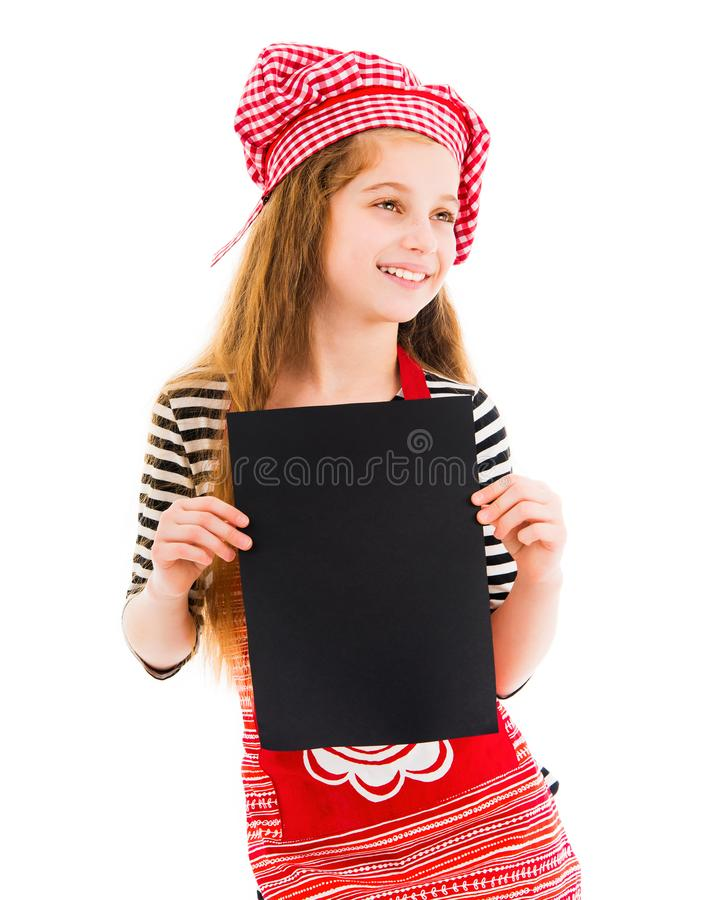 Little girl holds blank sheet of paper. Young little girl in red chef uniform holds vertical blank black sheet of paper and smiles isolated on white background stock photo