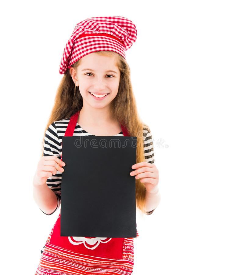 Little girl holds blank sheet of paper. Young little girl in red chef uniform holds vertical blank black sheet of paper and smiles isolated on white background royalty free stock photography