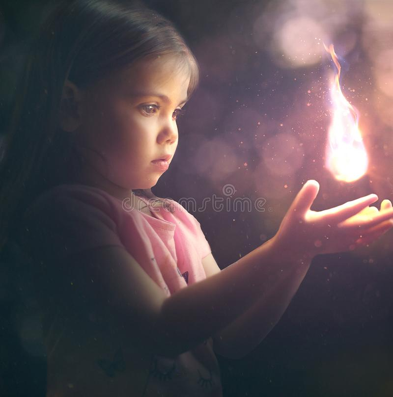 Little girl holding a light. A little girl holds a bright glowing light stock photos