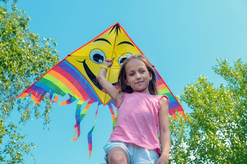 The little girl holds a bright kite in her hands and smiles against the blue sky. Concept of summer, freedom and happy childhood royalty free stock image