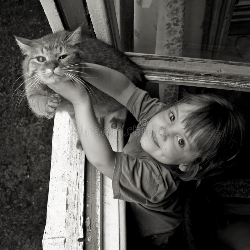 Little girl holds the cat by posing to the photographer. Black and white photography royalty free stock images