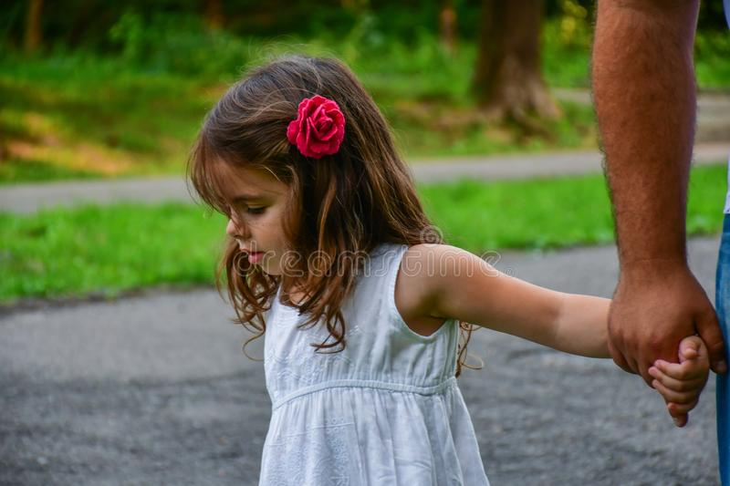The little girl holds by the hand with a flower in her hair royalty free stock image