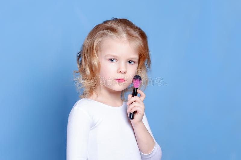 The little girl holds in her hand a brush for makeup. Beautiful baby with blond hair. Bright advertising photograph. stock images