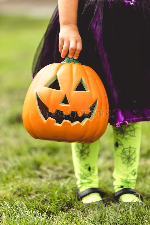 Little girl holds an orange jack o lantern Halloween decoration stock photography