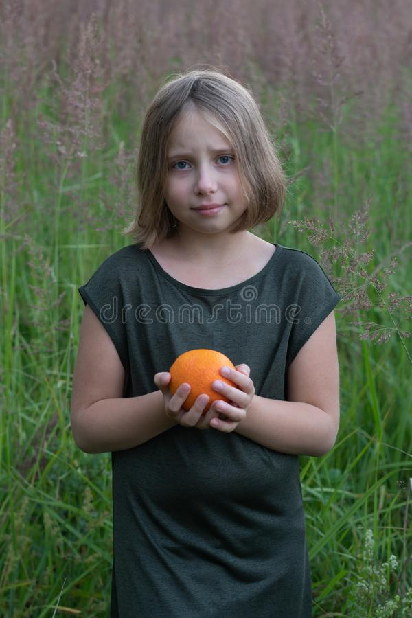 Little girl holds an orange. Stands outside in a green dress in a field royalty free stock photos