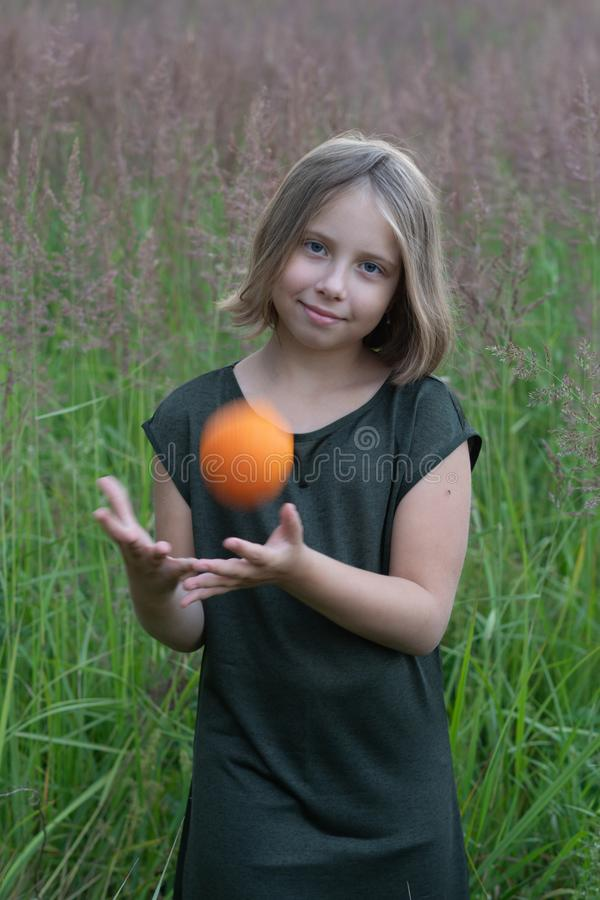 Little girl holds an orange. Stands outside in a green dress in a field stock photos