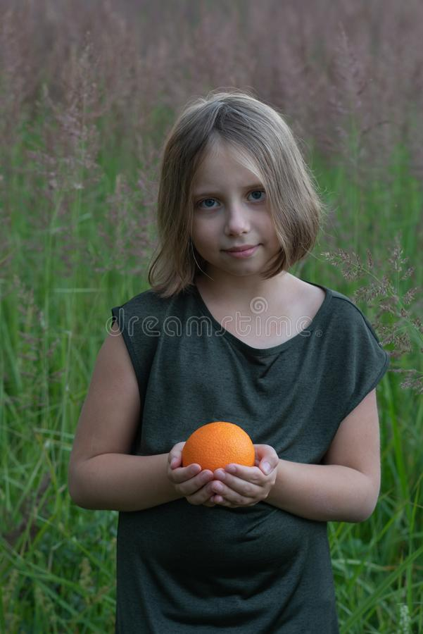 Little girl holds an orange. Stands outside in a green dress in a field royalty free stock photography