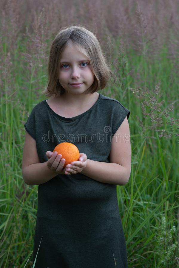 Little girl holds an orange. Stands outside in a green dress in a field royalty free stock photo