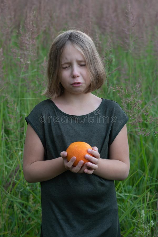 Little girl holds an orange. Stands outside in a green dress in a field stock photo