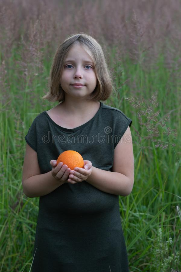 Little girl holds an orange. Stands outside in a green dress in a field stock images