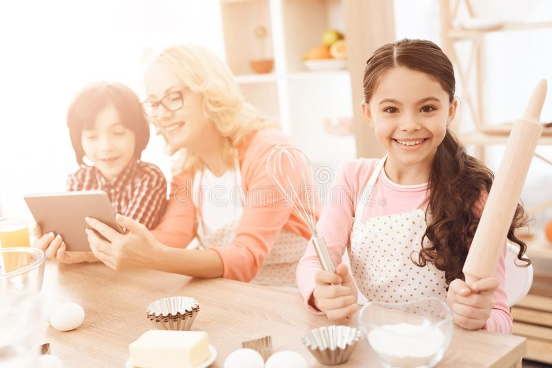 Little girl holds rolling pin and whisk in her hands, sitting in kitchen with her grandmother and grandson. royalty free stock image