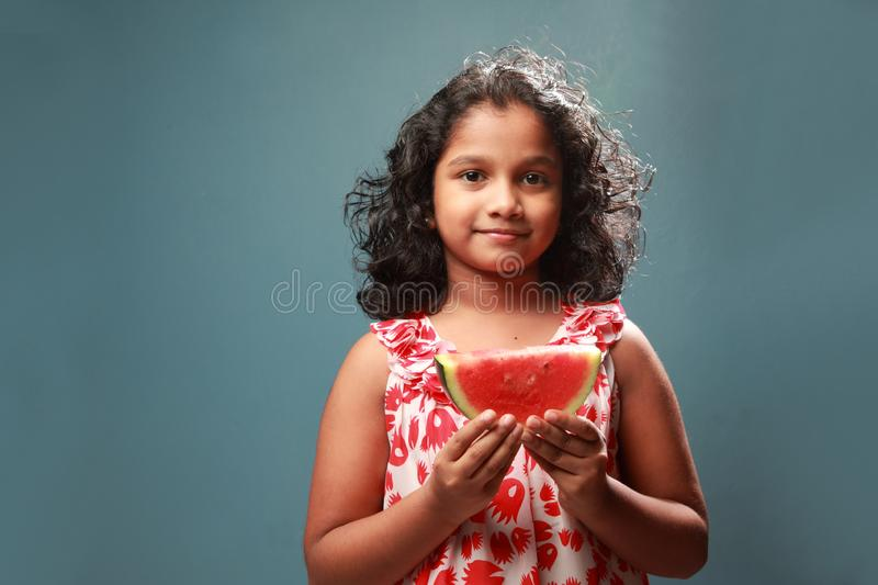 A little girl holds a slice of watermelon. Happy little girl holds a slice of watermelon royalty free stock photography