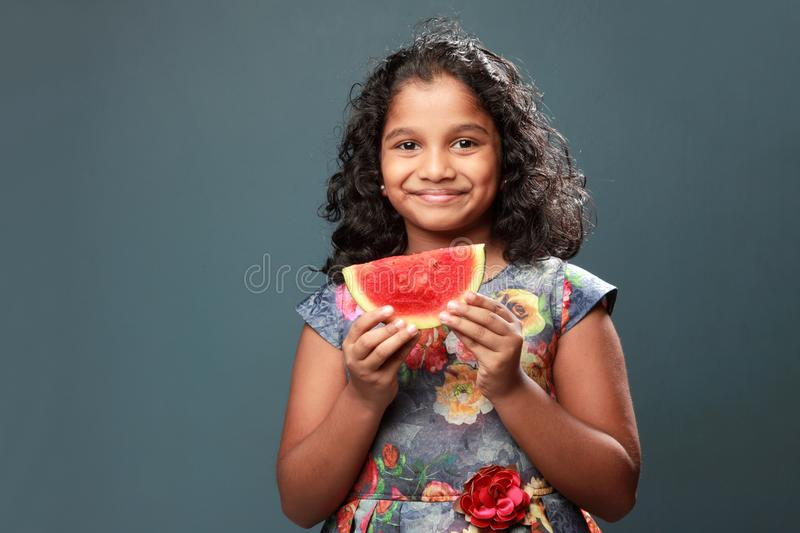 A little girl holds a slice of watermelon. Happy little girl holds a slice of watermelon stock images
