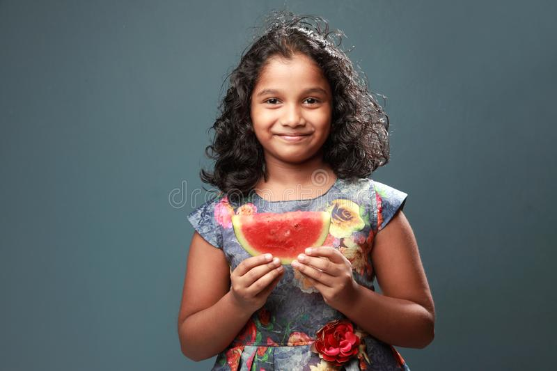 A little girl holds a slice of watermelon. Happy little girl holds a slice of watermelon stock photo