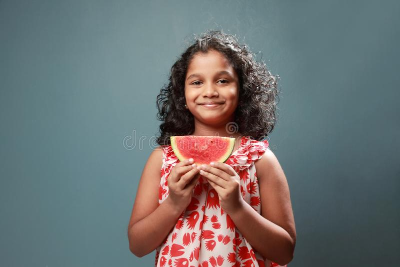 A little girl holds a slice of watermelon. Happy little girl holds a slice of watermelon royalty free stock photos